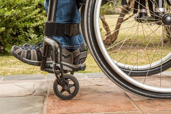 Shoes and wheels of person in wheelchair